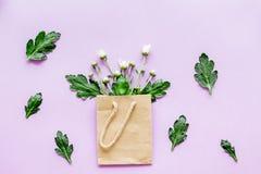 蝴蝶下落花卉花重点模式黄色 在一个纸袋的花束在紫色背景顶视图 免版税图库摄影