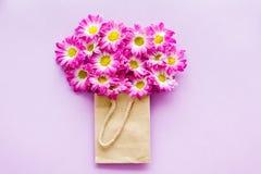 蝴蝶下落花卉花重点模式黄色 在一个纸袋的花束在紫色背景顶视图copyspace 图库摄影