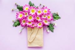 蝴蝶下落花卉花重点模式黄色 在一个纸袋的花束在紫色背景顶视图copyspace 免版税库存照片