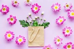 蝴蝶下落花卉花重点模式黄色 在一个纸袋的花束在紫色背景顶视图copyspace 免版税图库摄影