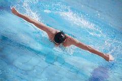 蝴蝶盖帽执行的冲程游泳者 免版税图库摄影