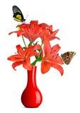 蝴蝶坐在红色花瓶的百合 免版税库存图片