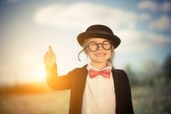 蝶形领结的滑稽的小女孩和显示赞许的圆顶硬礼帽 免版税库存图片