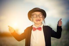 蝶形领结的滑稽的小女孩和显示赞许的圆顶硬礼帽 库存图片