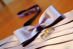 蝶形领结、婚姻的传送带和圆环在桌上说谎 图库摄影