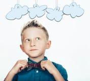 蝶形领结的小男孩与动画片在白色覆盖 图库摄影
