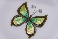 蝴蝶由棕色金属制成在老,明亮的木墙壁 免版税图库摄影