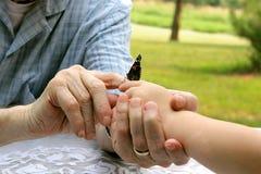 给蝴蝶的祖父的手孩子 库存照片