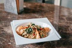 融合面团辣泰国垫Kapraw意粉用大蒜、红色辣椒、虾和圣洁蓬蒿在白色板材 免版税图库摄影