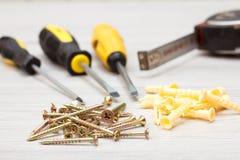 螺丝刀、卷尺和螺丝在白色木背景 图库摄影