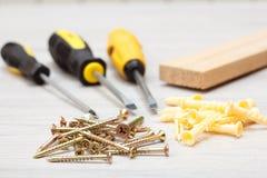 螺丝刀、木块和螺丝在白色木背景 库存图片