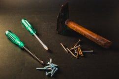 螺丝刀、螺丝、钉子和锤子在深灰背景 图库摄影