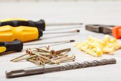 螺丝刀、钻子、钳子和螺丝在白色木backgroun 免版税库存照片