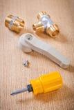 螺丝刀和在木板的水龙头装置 免版税库存照片
