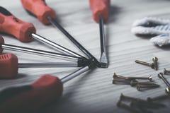 螺丝刀和套在木背景的螺丝 库存图片