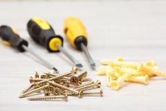 螺丝刀和螺丝在白色木背景 免版税库存图片