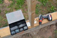 螺丝刀和钉子螺丝塑料盒在新的基础 免版税库存图片