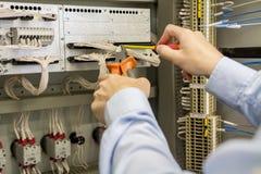螺丝刀和钢丝钳在电工的手上反对电箱子有终端、导线和控制器的 免版税库存照片