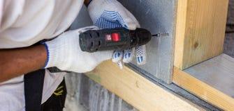 螺丝刀转动螺丝 混凝土墙 房子的建筑 免版税库存照片