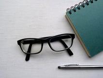 螺旋装订的笔记本、玻璃和笔 库存图片