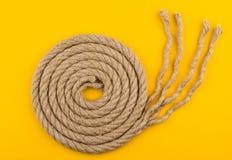 绳索螺旋顶视图与被解开的末端的在黄色背景 免版税图库摄影