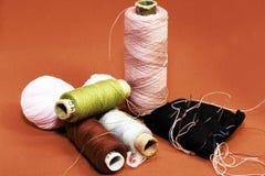 螺纹、毛线和小枕头有mongles的在红色背景 库存图片
