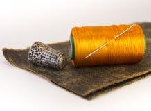 螺纹五颜六色的卷在一块皮革的与针和顶针的 免版税库存照片