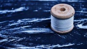 螺纹短管轴在桌上的 在一个卷轴的螺纹工艺的 Ma 库存照片