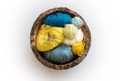螺纹羊毛剪和球在顶上木的碗的 免版税库存图片