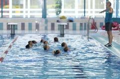 蠢材 小组孩子在水池学会游泳 库存照片