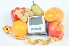 血压显示器、新鲜的成熟果子与菜和厘米,健康生活方式 免版税库存图片