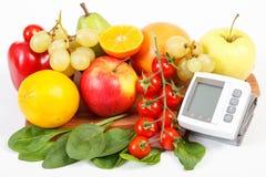 血压显示器和新鲜的成熟果子与菜,健康生活方式 库存图片