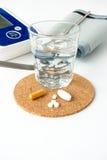 血压显示器和药片 免版税库存图片