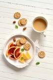 血橙、乳酪和薄脆饼干在葡萄酒板材 库存图片