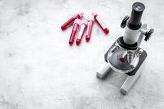 血液分析在clinacal实验室 在显微镜附近的试管在灰色背景顶视图拷贝空间 免版税库存照片