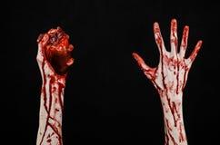 血液和万圣夜题材:可怕的血淋淋的在黑背景隔绝的手举行被撕毁的流血的人的心脏在演播室 库存图片