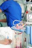 血液流失容器和工作的医生在耐心床附近 免版税图库摄影