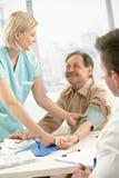 血液评定的护士耐心压微笑 免版税图库摄影