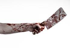血淋淋的万圣夜题材:拿着在白色背景的血淋淋的手一把大血淋淋的厨刀被隔绝 库存照片