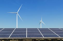 行一些多晶的硅太阳电池板和发在杂种能源厂系统驻地的风轮机电 库存图片