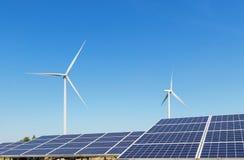 行一些多晶的硅太阳电池板和发在杂种能源厂系统驻地的风轮机电 库存照片