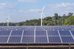 行一些多晶的硅太阳电池板和发在杂种能源厂系统驻地的风轮机电 免版税库存照片