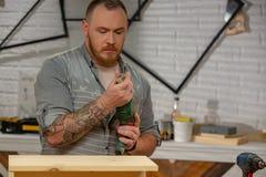 行业、木匠业、木制品和人概念-木匠在工作前调整钻子在车间 免版税库存照片