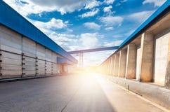 行业大商店 在蓝色仓库之间的街道有日落的 球尺寸三 图库摄影