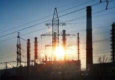 行业横向 在输电线和管子的日落结合热能和动能植物 免版税库存图片
