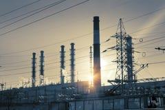 行业横向 在输电线和管子的日落结合热能和动能植物 库存图片