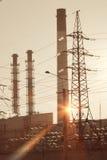 行业横向 在输电线和管子的日落结合热能和动能植物 免版税库存照片
