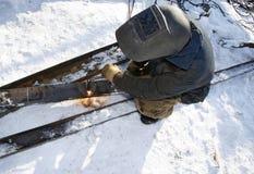 钻行业油西伯利亚适当的西部 产业工人在室外的冬天使用乙炔火炬 免版税库存图片