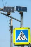 行人交叉路标志、红绿灯和太阳电池板在城市街道上 库存图片