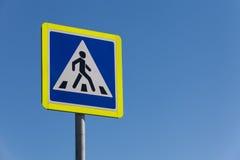 行人交叉路标志在反对天空的一个晴天 免版税库存照片